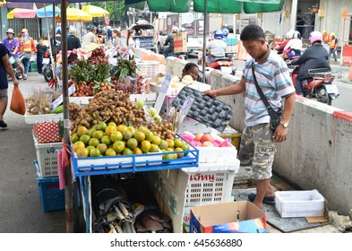 BANGKOK, THAILAND- MAY 19, 2017: Unknown seller who sells fresh local fruit on the street in Bangkok, Thailand.