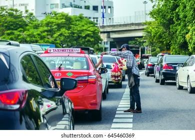 Bangkok, Thailand May 19th, 2017; A man who selling flower garland to a taxi on the Pradidmanutham road to Pradidmanutham intersection Bangkok Thailand when the cars are stopped for red light traffic
