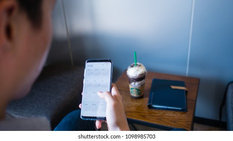 Bangkok, Thailand - May 19th 2018 : A man use Samsung S9 plus show calendar 2018 on screen with Starbucks coffee and black note book on the wooden table.