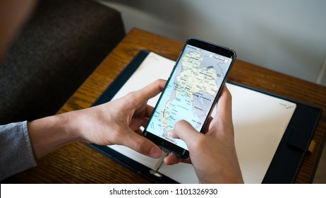 Bangkok, Thailand - May 19th 2018 : A man use Samsung S9 plus show thailand map on screen and note book on the wooden table.