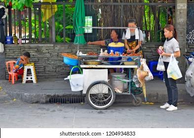 Bangkok, Thailand - May 2, 2017: Street food vendor wheeling cart on Sukhumvit Soi 11.