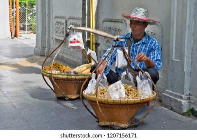Bangkok, Thailand - May 2, 2017: Peanuts vendor squatting behind his balancing basketson a sidewalk.