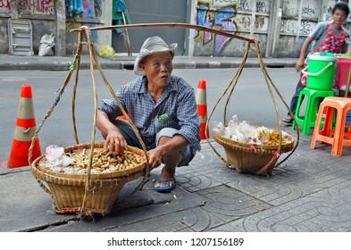 Bangkok, Thailand - May 2, 2017: Peanuts vendor squatting behind his balancing baskets on a sidewalk of Sukhumvit Soi 4.