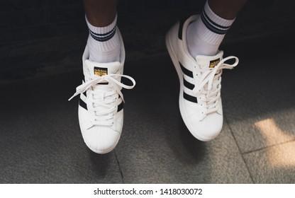 Bangkok, Thailand - May 20, 2019: a closeup of white Adidas Superstar sneakers on men's feet.