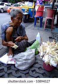 BANGKOK, THAILAND - MAY 20: Thai elderly woman sells paper fish on sticks on the street on May 20, 2008 in Bangkok.