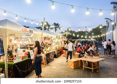 BANGKOK, THAILAND - May 2018 - People sitting on wooden chairs,walking,eating and buying food at street food market festival in a park. Market Stalls. Shopping. Outdoor Market. Food Event. Food Fair.
