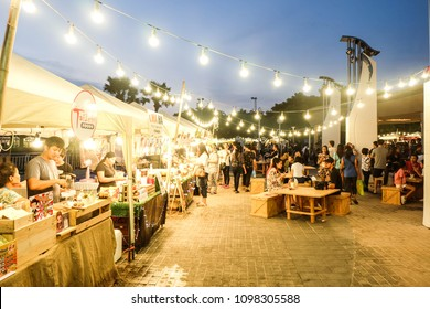 BANGKOK, THAILAND - May 2018 - People and Tourist sitting,walking,eating and buying food at night street food market festival in a park. Market Stalls. Outdoor Market. Food Event. Food Fair. Festival.