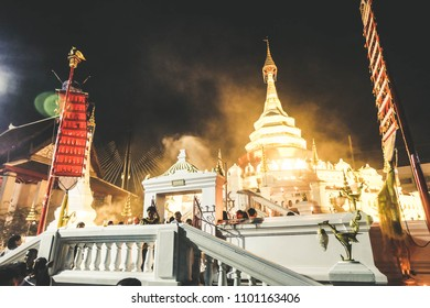 BANGKOK, THAILAND - May 2018 - Thai Buddhist hold the fired candle in hand and lotus flower walking around temple (pagoda) on Visakha Puja Day. Vortex. Buddhist Holy Day. Making merit.