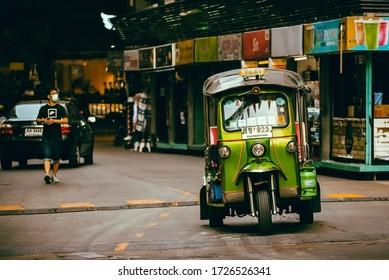 BANGKOK, THAILAND - MAY, 2020: green tuk tuk in a sidestreet of Silom taking passengers. Street Kiosks on the background.