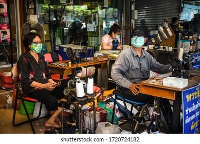 BANGKOK, THAILAND - MAY, 2020: thai street tailors wearing masks during outbreak of COVID-19