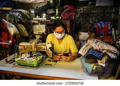 BANGKOK, THAILAND - MAY, 2020: thai female street tailor wearing surgical mask and chatting on mobile phone, sitting by old sewing machine with a kid playing mobile pad/tab at the back.