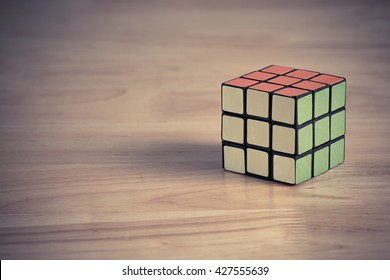 BANGKOK, THAILAND - MAY 24, 2016: Rubik's cube on the wood background. Rubik's cube on the wood background. Rubik's Cube invented by a Hungarian architect Erno Rubik in 1974.