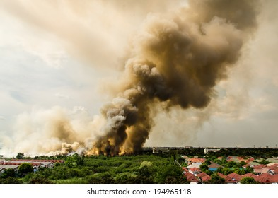 Bangkok, Thailand - May 25, 2014: Forest fires in the city, causing a large flame and smoke in the air is very hot days. Firemen rush to help prevent the spread of fire to the village., In Thailand.