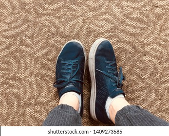 BANGKOK, THAILAND, MAY 27, 2019: the guy wears shoes branded Sketchers, stands on the carpet floor.