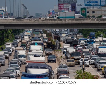 Bangkok, Thailand - May 28, 2018: Traffic jam on Kanchana Phisek Road, the ring road around Bangkok, in 35 degrees Celsius. The heat is so strong that it is visible as haze distortion in the photo.
