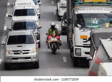 Bangkok, Thailand - May 28, 2018: Police motorbike manouvering through a traffic jam on Kanchana Phisek Road, the ring road around Bangkok, at Talat Bang Yai in 35 degrees Celsius.