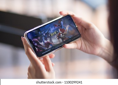 BANGKOK, THAILAND - May 29, 2018. Realm of valor (ROV) or Arena of valor (AOV) game application display on mobile screen in female hand's while login to play arena of valor or realm of valor