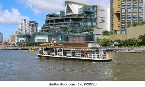 BANGKOK, THAILAND - MAY 29, 2021: Shuttle boat on the Chao Phraya river in front of luxury shopping mall Iconsiam on May 29, 2021 in the Thai capital Bangkok