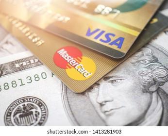 BANGKOK, THAILAND - May 29,2019: Closeup shot of VISA credit card, JCB credit card and Master Card credit card with ten dollar bank notes