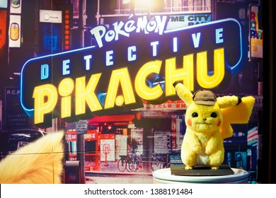 Bangkok, Thailand - May 4, 2019 : A photo of Pokemon Detective Pikachu movie standee in front of theatre to promote movie Detective Pikachu. Soft focus on a realistic Pikachu plush doll.