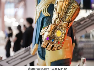 Bangkok, Thailand - May 4, 2019 :  A closed up photo of Thanos's infinity gauntlet, gold glove with luminous stones. Thanos is a super villain from Avengers movie, production by Marvel Studio.