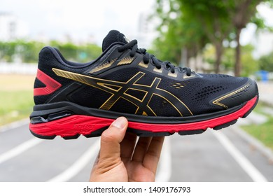 Bangkok, Thailand - May 4, 2019 :Hand holding ASICS Running Shoes GT-2000 7, ASICS is a Japanese multinational corporation athletic equipment company which produces footwear and sports equipment
