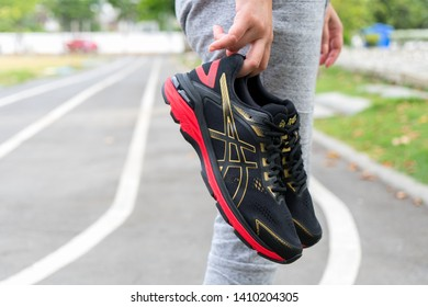 Bangkok, Thailand - May 4, 2019 :Woman Hand holding ASICS Running Shoes GT-2000 7, ASICS is a Japanese multinational corporation athletic equipment company which produces footwear and sports equipment