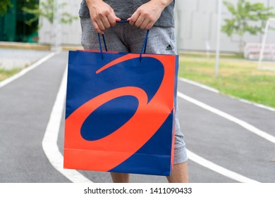 Bangkok, Thailand - May 4, 2019 : Woman holding ASICS shot outdoor, ASICS is a Japanese multinational corporation athletic equipment company which produces footwear and sports equipment.
