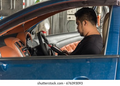 Bangkok, Thailand - May 5, 2017 : Unidentified car mechanic or serviceman checking a car engine by OBD-II electric tools for fix and repair problem at car garage or repair shop