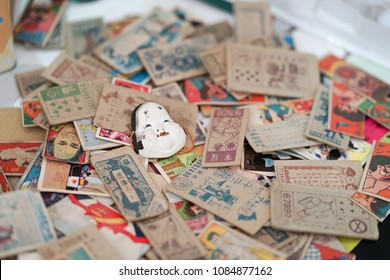 Bangkok, Thailand - May 5, 2018 : A photo of vintage Japanese items and old Japanese cards scattered on the floor with soft focus on the vintage Japanese mask. Editorial use only.
