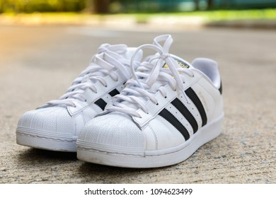BANGKOK, THAILAND - MAY 5, 2018 : Adidas Superstar shoe white color stripes black with popular fashion Thailand on street floor in urban