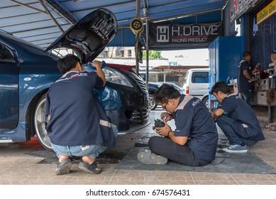 Bangkok, Thailand - May 6, 2017 : Unidentified car mechanic or serviceman checking a car headlight for fix and repair problem at car garage or repair shop
