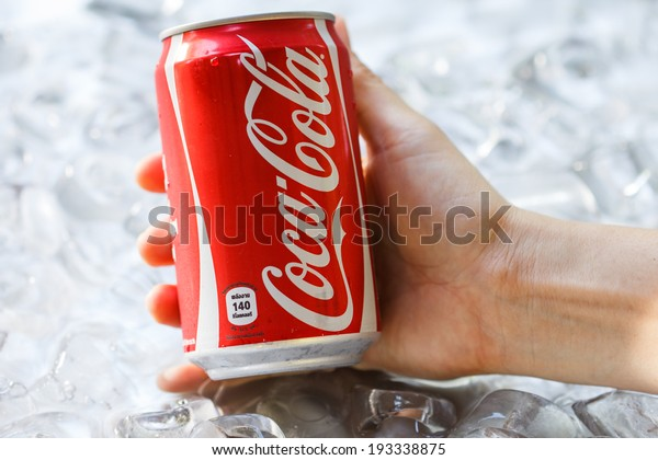 BANGKOK, THAILAND - MAY 8, 2014 : Can of Coca-Cola lying on ice. Coca-Cola is the one of the worlds favourite soft drinks.