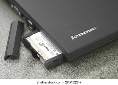 Bangkok, Thailand - May 9, 2015: Seagate HDD partially pop out of black Lenovo laptop slot over working desk