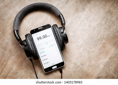 BANGKOK, THAILAND - May 19, 2019 : Mobile phone with 99.00 MHz radio app on screen and headphone put on a wooden table,Image with retro filter.