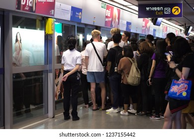 Bangkok, Thailand - Nov. 20, 2018: A group of tourists waiting for the MRT subway in the evening rush hour along with other commuters while official standing by to give safety advices.