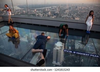 Bangkok, Thailand - Nov 21, 2018: Tourists lie on glass floor on rooftop of the King Power Mahanakhon building high above Bangkok, currently Thailand's tallest at 314 meters.