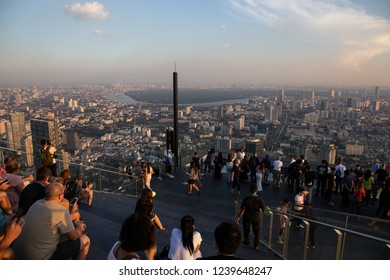Bangkok, Thailand - Nov 21,2018: Tourists enjoy sunset on rooftop of the King Power Mahanakhon building high above Bangkok, currently Thailand's tallest at 314 meters.