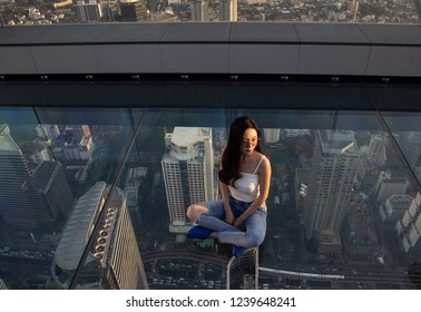 Bangkok, Thailand - Nov 21,2018: A woman sits on glass floor on rooftop of the King Power Mahanakhon building high above Bangkok, currently Thailand's tallest at 314 meters.