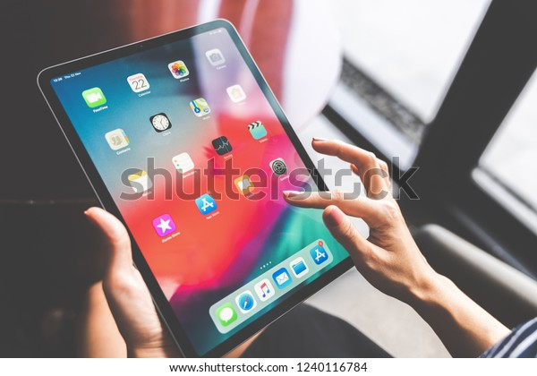 Bangkok, Thailand - Nov 22, 2018: Asian woman using the new 11 inch Apple iPad pro 2018, swiping home screen or touching app icon. Illustrative editorial content