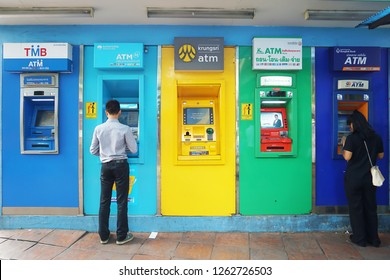 Bangkok, Thailand - NOV 30, 2018 : Man and woman using ATM (Automated Teller Machine) units of several banks in Thailand.