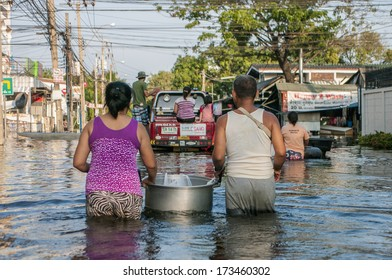 Bangkok - Thailand, Nov 6, 2011: A woman and her husband carrying a food for their child along Soi Chinnakhet, Ngamwongwan road during a big flooding in Thailand