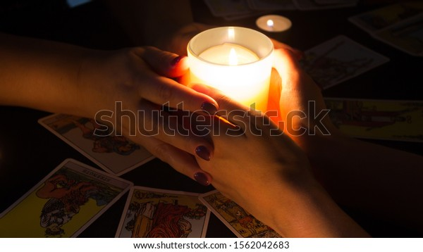 Bangkok, Thailand, Nov.17.19. Ritual of enchantment and clairvoyance. Seance and prediction of the future. Female hands hold a lighted candle in the dark at night. A fortune teller performs a magical