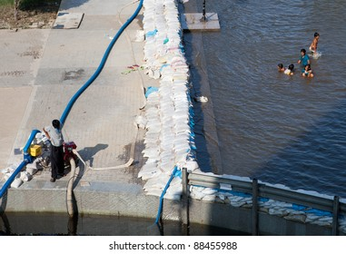 BANGKOK, THAILAND - NOVEMBER 04: unidentified Children swimming at a sandbag wall at the Chao Phraya river on November 04, 2009 in Bangkok, Thailand. During Thailand's worst monsoon flood in 20 years
