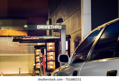 BANGKOK, THAILAND - NOVEMBER 04: A white car drives into a Mcdonald's DriveThru in the evening in Bangkok on November 04, 2017.