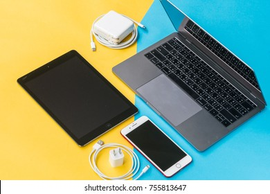 BANGKOK, THAILAND - November 05, 2017: Apple Inc. device products Macbook Pro, iPhone, iPad on yellow and blue background in flat lay or top view