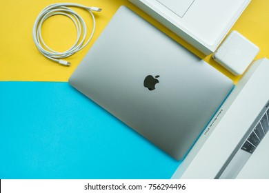 BANGKOK, THAILAND - November 05, 2017: Apple Inc. product design Space gray Macbook Pro on yellow and blue background in flat lay or top view