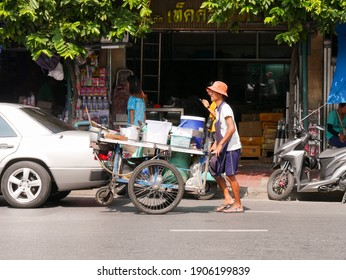 Bangkok, Thailand - November 08, 2019: Thai street food vendor pushing a handcart on the street in Bangkok.