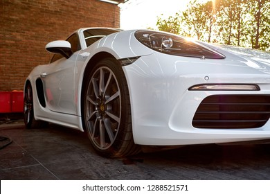 BANGKOK, THAILAND - NOVEMBER 1, 2018: Front view of white Porsche Cayman with headlight & fender details. Modern luxury sports car with reflection on paint after wash & wax. Car detailing background.
