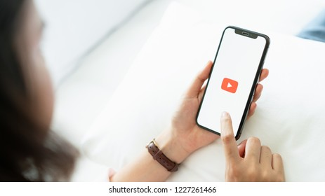 Bangkok, Thailand - November 12, 2018 : hand is pressing the screen displays the Youtube app icons on Apple iPhone. YouTube is the popular online video-sharing website.